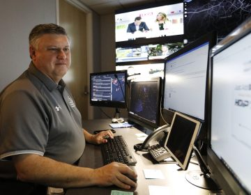 In this July 30, 2019, photo, Paul Hildreth, emergency operations coordinator for the Fulton County School District, works in the emergency operations center at the Fulton County School District Administration Center in Atlanta. Artificial Intelligence is transforming surveillance cameras from passive sentries into active observers that can immediately spot a gunman, alert retailers when someone is shoplifting and help police quickly find suspects. (Cody Jackson/AP Photo)