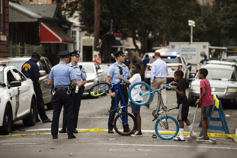 Children visit with officers as officials conduct an investigation at the scene of Wednesday's standoff with police in Philadelphia, Thursday, Aug. 15, 2019. The gunman, identified as Maurice Hill, wounded six police officers before surrendering early Thursday, after an hours-long standoff. (Matt Rourke/AP Photo)