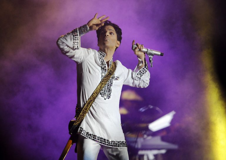 In this April 26, 2008 file photo, Prince performs during his headlining set on the second day of the Coachella Valley Music and Arts Festival in Indio, Calif.  Fifty years at Woodstock, the mystical and messy event that became the father of all musical festivals, the entertainment industry is diluted with festivals and events like it, some genre specific, some extremely diverse and others offering experiences in addition to music, ranging from food to art, in order to appeal to wider audiences.(Chris Pizzello/AP Photo)