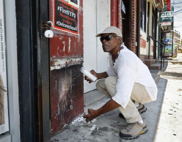 Doug Brinson collects candles to prevent a fire at the make-shift memorial, Tuesday, Aug. 20, 2019, where Eric Garner died in a police chokehold five years ago, in the Staten Island borough of New York. (Richard Drew/AP Photo)