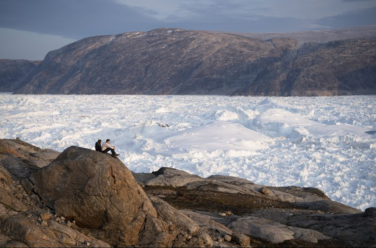 In this Aug. 16, 2019, photo, New York University student researchers sit on a rock overlooking the Helheim glacier in Greenland.  U.S. President Trump announced his decision to postpone an early September visit to Denmark by tweet Tuesday Aug. 20, 2019, after Danish Prime Minister Mette Frederiksen dismissed the notion of selling Greenland to the U.S. as