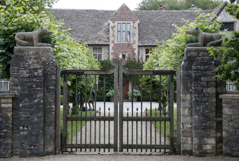 A gate protects the entrance of the Rooksnest estate near Lambourn, England, Tuesday, Aug. 6, 2019. The manor is the domain of Theresa Sackler, widow of one of Purdue Pharma's founders and, until 2018, a member of the company's board of directors. (Frank Augstein/AP Photo)
