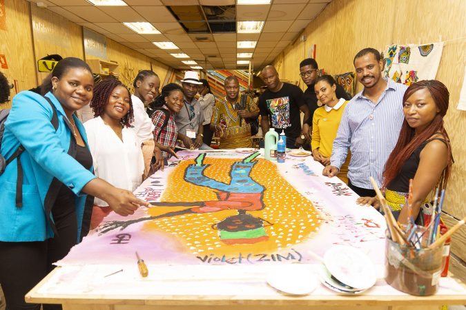 Mandela Washington Fellows pose with Chester Made Artistic Director, Devon Walls (center right), around their group painting of an African Stilt Walker created during the Chester Made and Mandela Washington Fellowship Exchange 2019. (Greg Irvin)