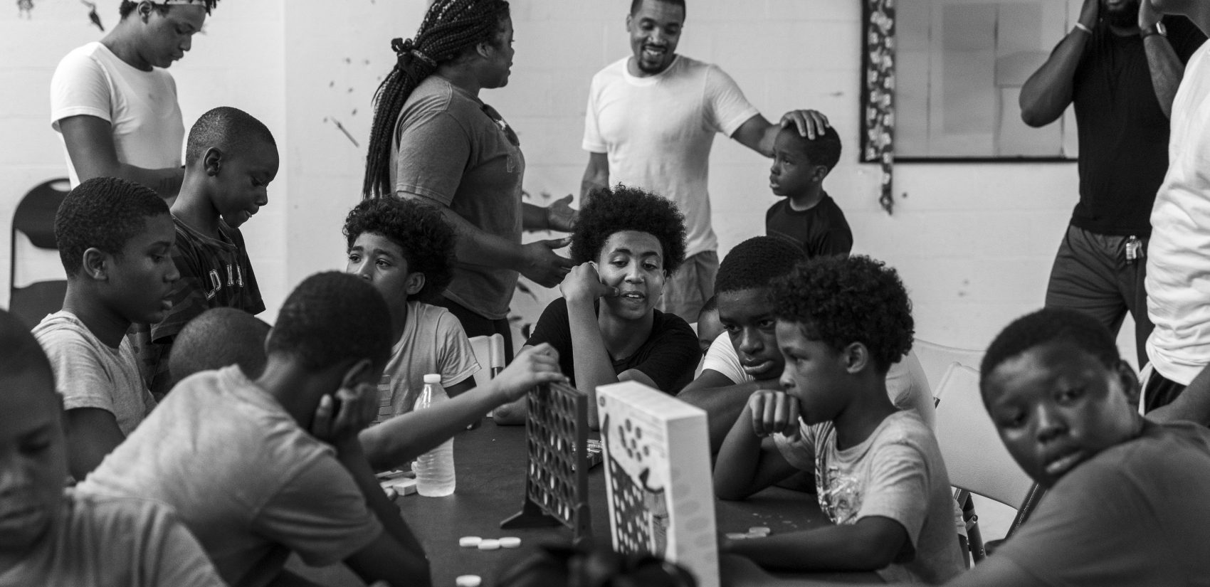 Rahdeem Abdullah (top center) connects with a student in the basement game room at Gathers. Shawn (center) watches younger kids in his role as a counselor in Aunt Cheryl's day camp. (Jessica Kourkounis for Keystone Crossroads)