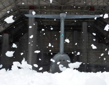 Wind-blown clumps of fire-suppression foam hang in the air outside of hangar 706 while the tail of a massive C-5M Super Galaxy can be seen inside the hangar at Dover Air Force Base, Del. (U.S. Air Force photo/Greg L. Davis)