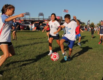 Young soccer fans play pickup games on the grass outside Lincoln Financial Field while waiting for the start of the U.S. Women's soccer game against Portugal. (Emma Lee/WHYY)