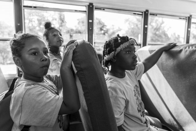 A yellow school bus takes kids from day camp on a trip to Fairmount Park. (Jessica Kourkounis for Keystone Crossroads)