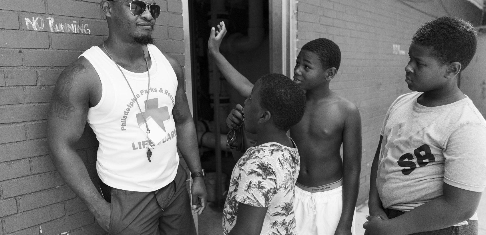 Gathers' head lifeguard Howard Bolden, 22, talks to kids on the pool deck.