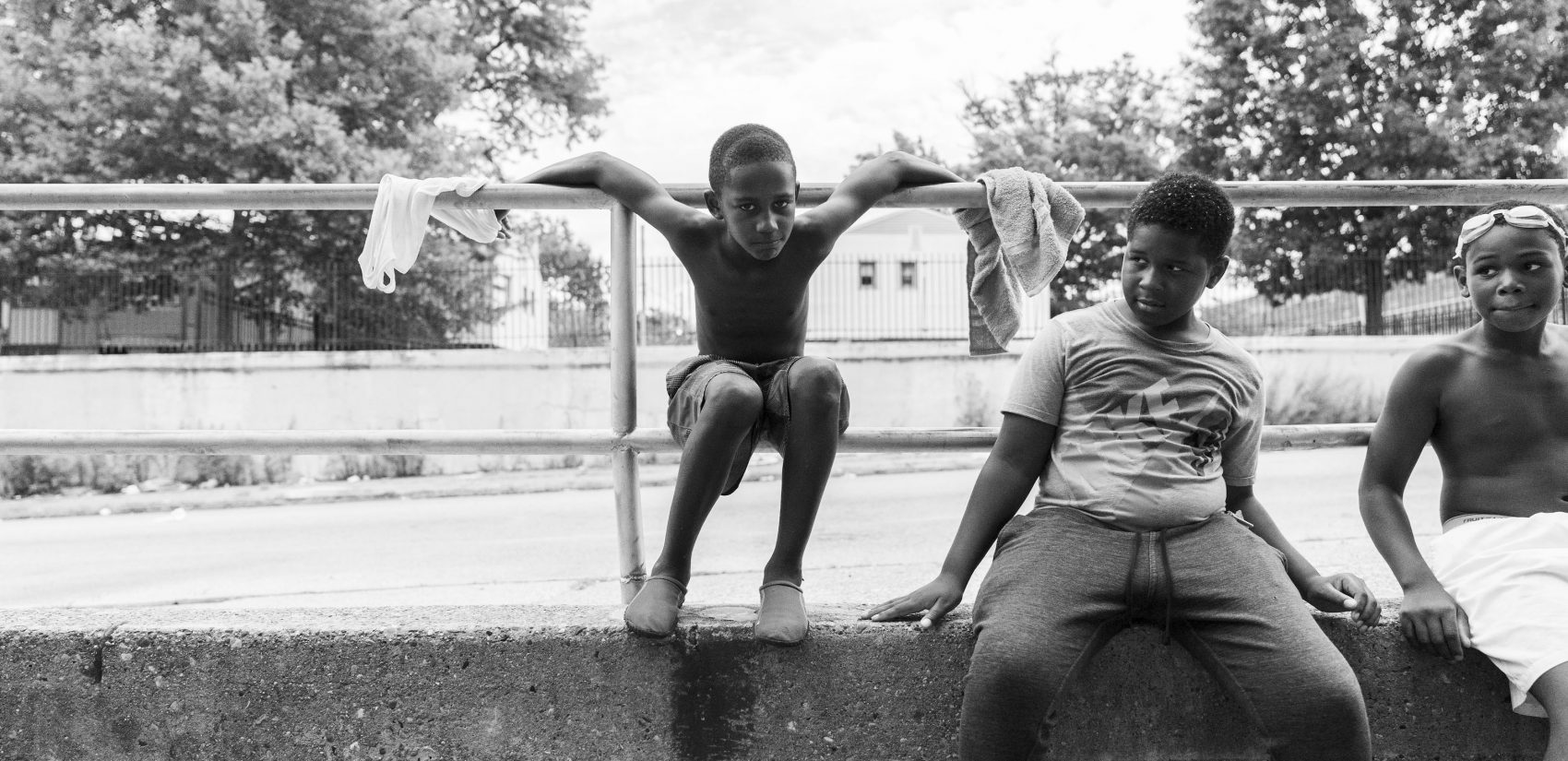 Kids hang out on the 25th Street side of the Hank Gathers Rec Center. Raymond Rosen Manor, a public housing complex, sits behind them. (Jessica Kourkounis for Keystone Crossroads)