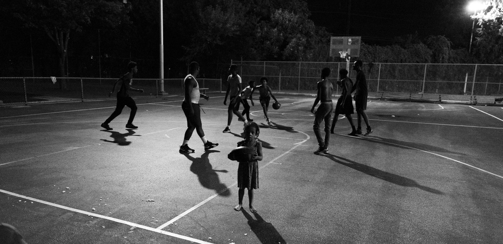 A young girl wanders onto the court during a night game at Gathers. (Jessica Kourkounis for Keystone Crossroads)