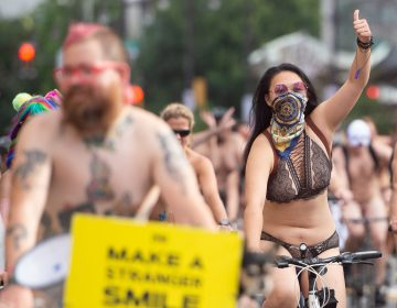 A rider gives a thumbs up to a cheering crowd during the Philly Naked Bike Ride. (Jonathan Wilson for WHYY)