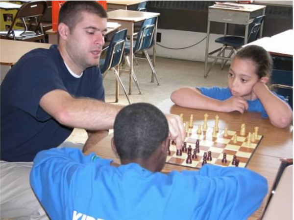 Marc Mannella teaches Zuleika Roman (right) chess in middle school. Zuleika was part of KIPP Philadelphia's first class in 2003. (Photo provided by KIPP Philadelphia Schools)