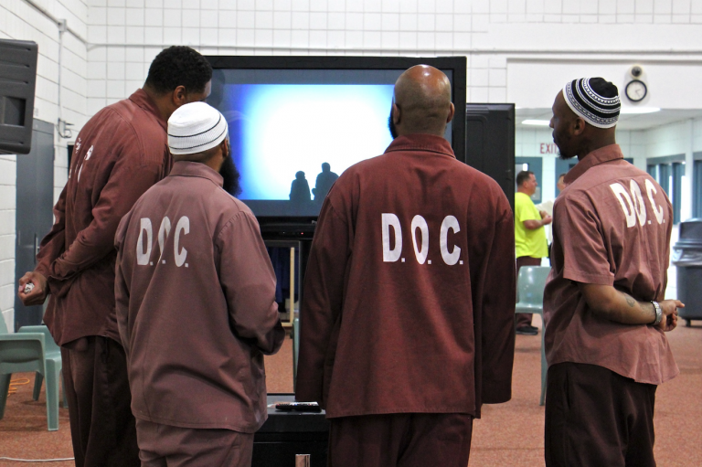 Inmates gather to watch the animated videos they created for 'Hidden Lives Illuminated,' a project of Eastern State Penitentiary. (Emma Lee/WHYY)