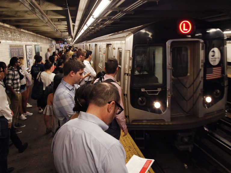 Straphangers wait for an L Train in New York City as it pulls into the First Avenue station. A bill under consideration might bar New York from replacing these cars with Chinese-made ones. (Mark Lennihan/AP)