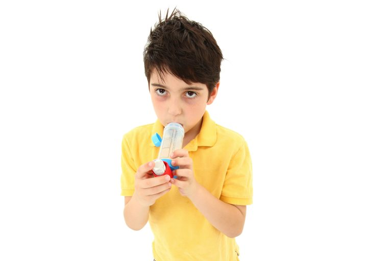 Sick young boy child using asthma inhaler with spacer chamber over white. Has periorbital hyperpigmentation.