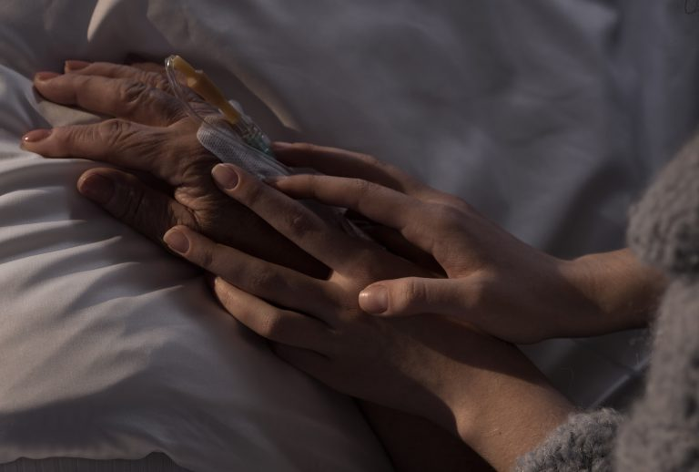 Photo of woman holding terminally ill mother hand