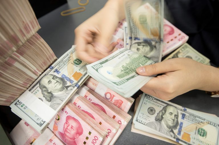 A Chinese bank employee counts 100-yuan notes and dollar bills at a counter in Nantong, in China's eastern Jiangsu province, on Tuesday. (AFP/Getty Images)