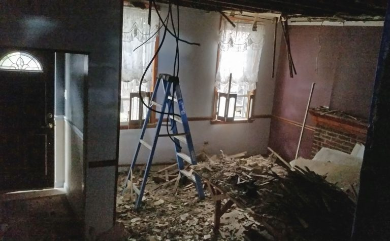 Removing plaster from the ceiling involves yanking it down onto your head, until you are calf-deep in broken plaster. (Peter Crimmins/WHYY)