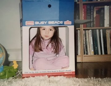Liz Tung, at 3 years old, pretends to be on television using a cardboard box. (Image courtesy of Liz Tung)
