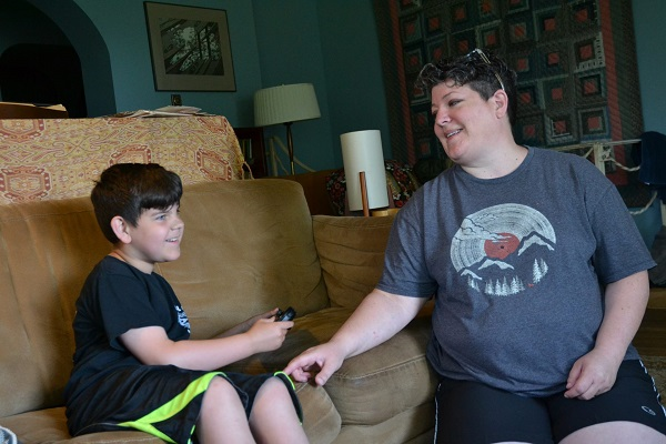 Owen Wagner, (left), smiles as he plays Mario Kart next to his mom, Gerren Wagner. Beginning in mid-August, Owen will lose his behavioral services through WellSpan. (Brett Sholtis/Transforming Health)