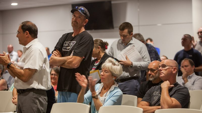 Jim Dougherty (second from left) waits in line for his turn to talk at the township meeting. (Emily Cohen for WHYY)