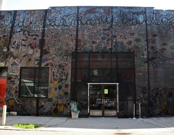 The Painted Bride Art Center is draped in black mesh since it was discovered that the Isaiah Zagar mural that covers it is separating from its walls. (Emma Lee/WHYY)