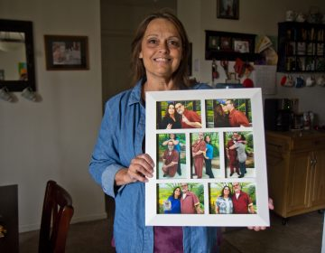 Joanne Schilk-Bierman holds framed photos from visits to her oldest brother Tom Schilk, who's serving a life sentence in prison. (Kimberly Paynter/WHYY)