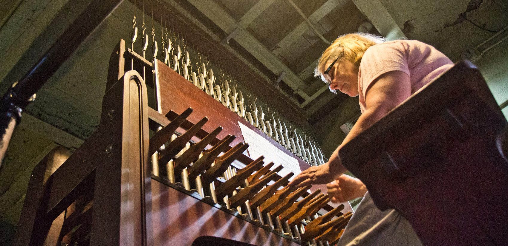 Janet Tebbel plays the carillon beneath the attached bells at the Miraculous Medal Shrine. (Kimberly Paynter/WHYY)
