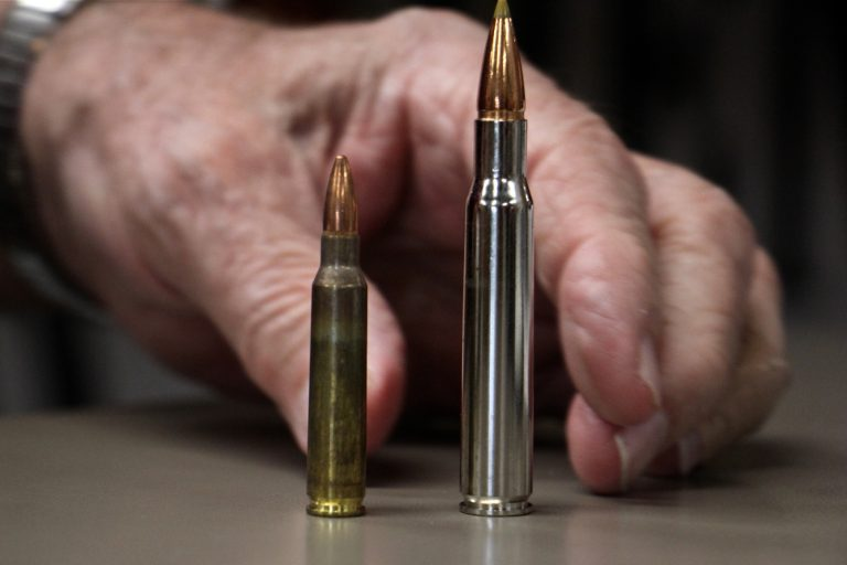 Bob Viden, owner of Bob's Little Sport Shop in Glassboro, compares the bullets used in the AR 15 (left) and the Remmington hunting rifle. The latter, he says, is more powerful and accurate, while the former is considered too weak to be used for deer hunting. (Emma Lee/WHYY)
