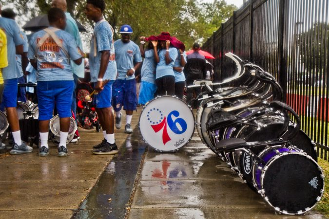 A drum line waits in the downpour to join the 2019 Labor Day Parade. (Kimberly Paynter/WHYY)