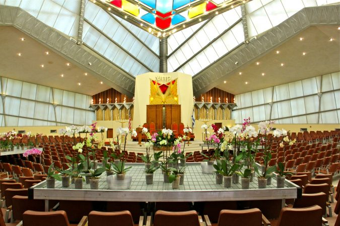 Visual artist David Hartt has installed an exhibit at Beth Sholom Synagogue in Elkins Park, designed in the 1950s by architect Frank Lloyd Wright. The exhibit includes tropical plants along with videos, tapestries, and music. (Emma Lee/WHYY)