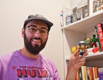 Shamus Clancy, Philadelphia writer and sports super fan, shows off his Carson Wentz bobble head toy at his apartment in South Philly. (Kimberly Paynter/WHYY)