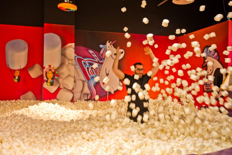 Adults play in the 'highly instagrammable' marshmallow pit at the Fashion District's Candytopia exhibit. (Kimberly Paynter/WHYY)
