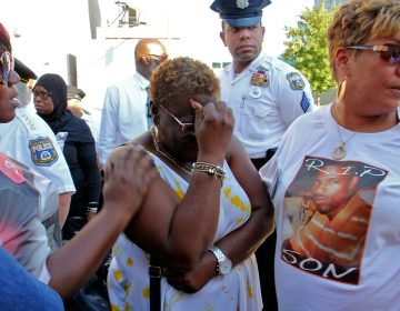 Sonya Dixon (center), whose two grandsons were murdered in 2017 and 2018, weeps during a demonstration outside the Philadelphia Police headquarters to call attention to unsolved murders. (Emma Lee/WHYY)