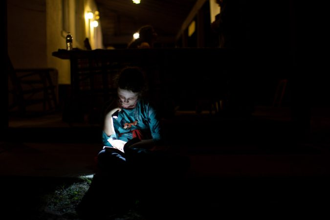 A girl reads by flashlight at