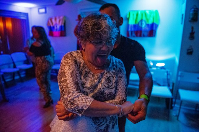 Milena Sanchez dances with her son, Einar Victoria, in a living room viejoteca on Saturday, September 14, 2019. (Kriston Jae Bethel for WHYY)