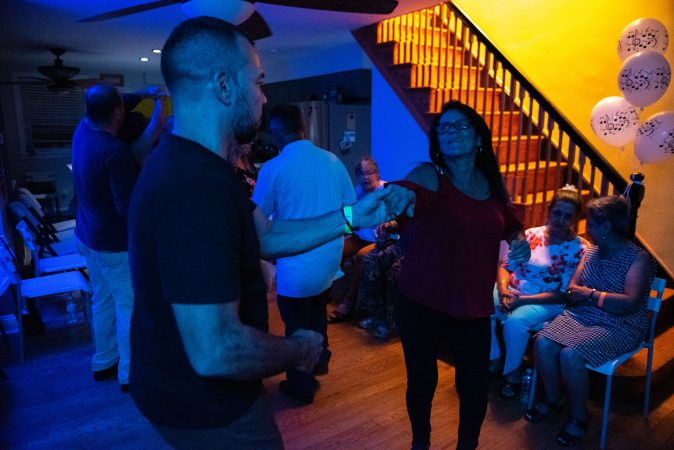 Guests dance to latin music in a living room-turned-viejoteca in Oxford Circle on Saturday, September 14, 2019. (Kriston Jae Bethel for WHYY)