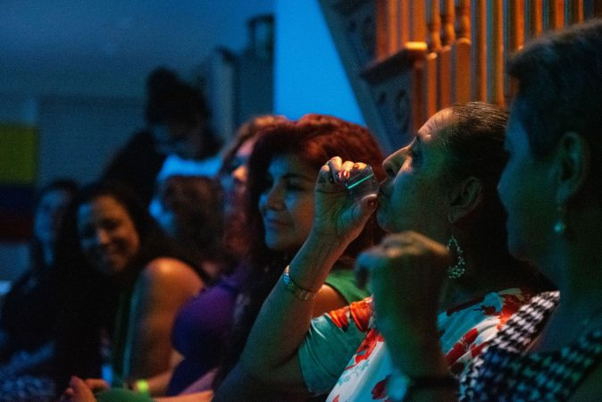 Mariela Bedoya takes a shot of tequilla during the vijoteca in Oxford Circle on Saturday, September 14, 2019. (Kriston Jae Bethell for WHYY)