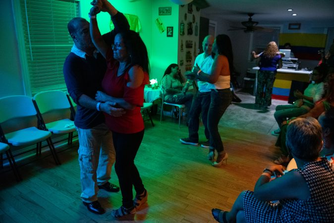 Guests dance in a viejoteca held in an Oxford Circle home on Sunday, September 15, 2019. (Kriston Jae Bethel for WHYY)