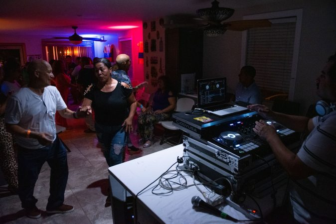 Guests dance from the kitchen to the living room at a viejoteca in Oxford Circle on Sunday, September 15, 2019. (Kriston Jae Bethel for WHYY)