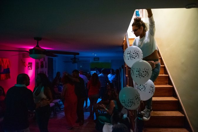 Kimberly Colon looks over the viejoteca dance scene hosted at her mother's home in Oxford Circle on Sunday, September 15, 2019. (Kriston Jae Bethel for WHYY)