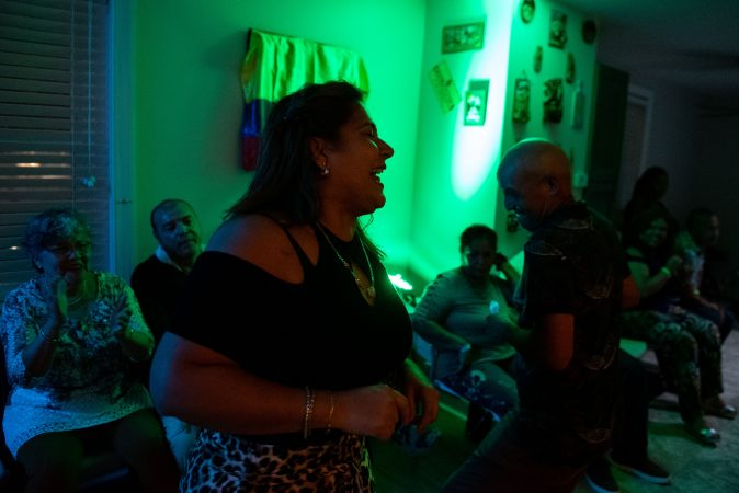 Sandra Colon laughs while dancing in the living room of her Oxford Circle home on Sunday, September 15, 2019. Colon regularly turns her home into a viejoteca (a dance party for older adults) after one restaurant in Philadelphia that hosted them closed down. (Kriston Jae Bethel for WHYY)