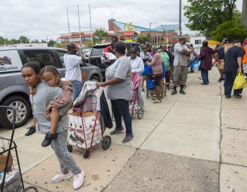 People queue up during a food giveaway at Dobbins High School in North Philadelphia this summer. (Avi Steinhardt/The Philadelphia Inquirer)