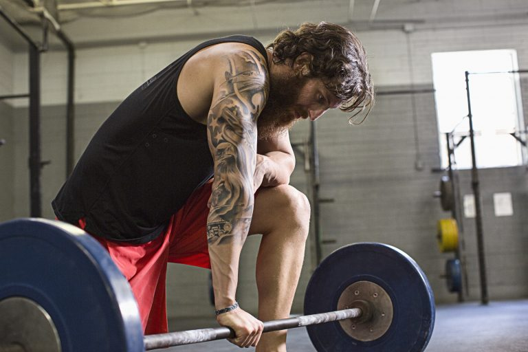 Athlete crouching at barbell in gym (Blend Images via AP Images)
