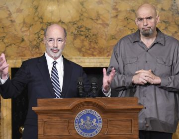 Pennsylvania Gov. Tom Wolf (left) and Lt. Gov. John Fetterman stand at a podium