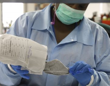 In this April 2, 2015, file photo, a forensic analyst removes a pair of underwear from an evidence bag for testing in a sexual assault case in the biology lab at the Houston Forensic Science Center in Houston, Texas. (Pat Sullivan/AP Photo, File)