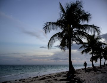 A woman walks along a beach before the arrival of Hurricane Dorian in Freeport, Grand Bahama, Bahamas, Saturday Aug. 31, 2019. Hurricane Dorian is closing in on the northern Bahamas, threatening to batter the normally idyllic islands with fierce winds, pounding waves and torrential rain. (Ramon Espinosa/AP Photo)