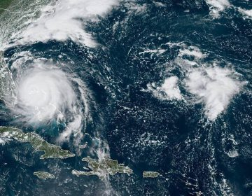 This GOES-16 satellite image taken Monday, Sept. 2, 2019, at 16:40 UTC and provided by National Oceanic and Atmospheric Administration (NOAA), shows Hurricane Dorian, (left), churning over Bahamas. Hurricane Dorian hovered over the Bahamas on Monday, pummeling the islands with a fearsome Category 4 assault that forced even rescue crews to take shelter until the onslaught passes. (NOAA via AP)