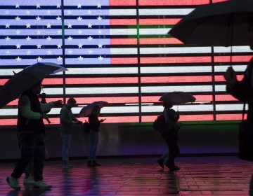 Visitors to New York's Times Square use umbrellas to shield themselves against the rain
