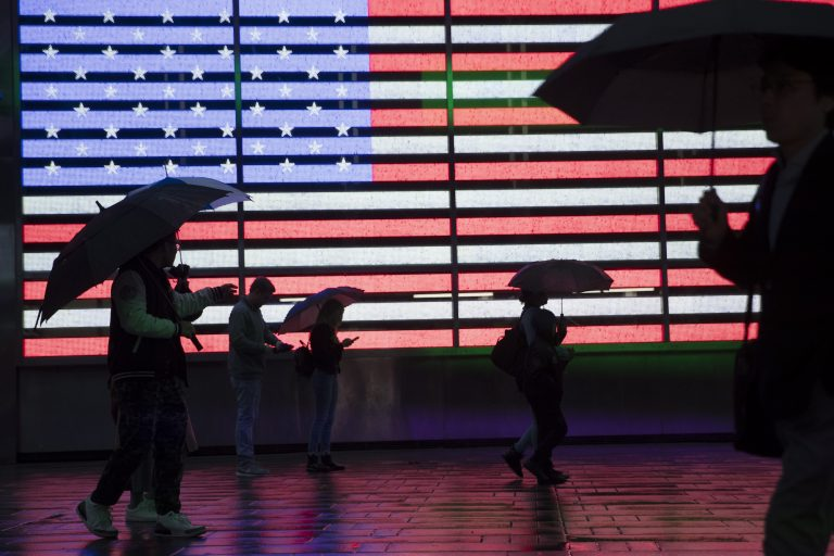 Visitors to New York's Times Square use umbrellas to shield themselves against the rain as they walk past the Armed Forces Recruitment Center, Friday, April 26, 2019. (Mary Altaffer/AP Photo)